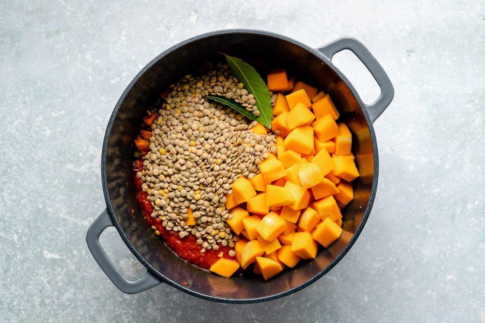 Prepping the lentil soup for simmering - crushed tomatoes, brown lentils, butternut squash & bay leaves added to large gray dutch oven atop a light blue surface.