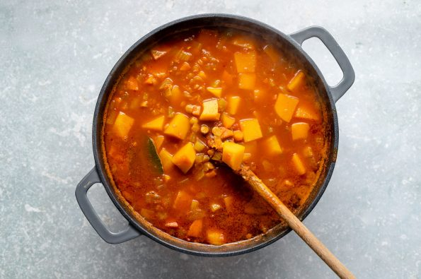 Wooden spoon stirs cooked lentil soup in a large grey dutch oven atop a light blue surface.