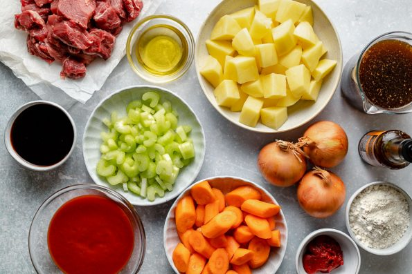 Hawaiian beef stew ingredients arranged on a light blue surface – cubed beef, soy sauce, tomato sauce, celery, carrots, potatoes, onions, tomato paste, flour, beef stock & Worcestershire.