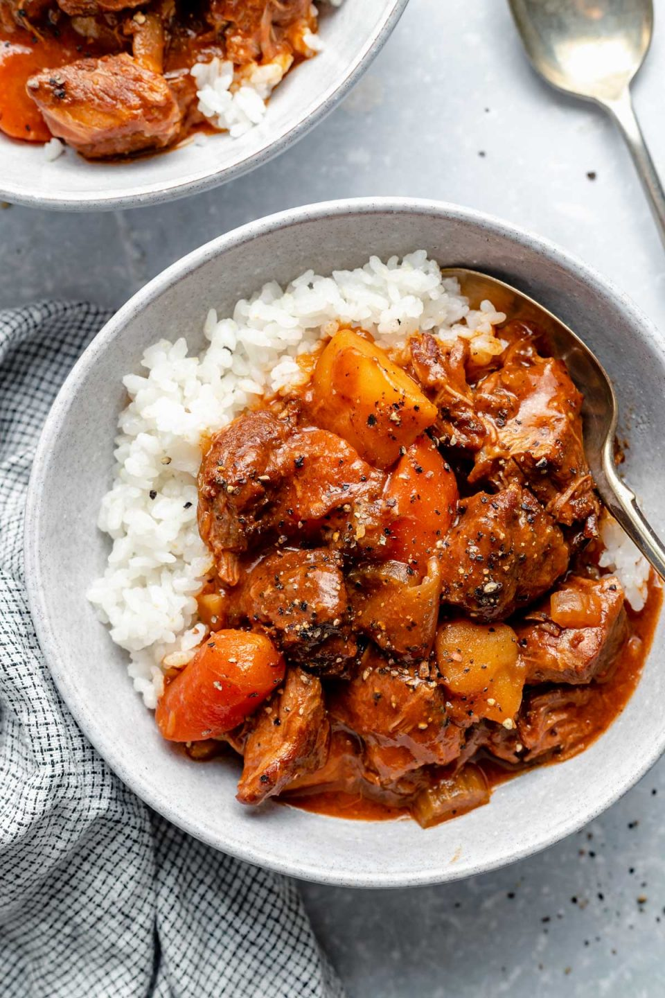 Hawaiian style beef stew over sticky rice in a large bowl, which sits atop a light blue surface next to a checkered linen napkin, a spoon, & a second bowl of Hawaiian beef stew.