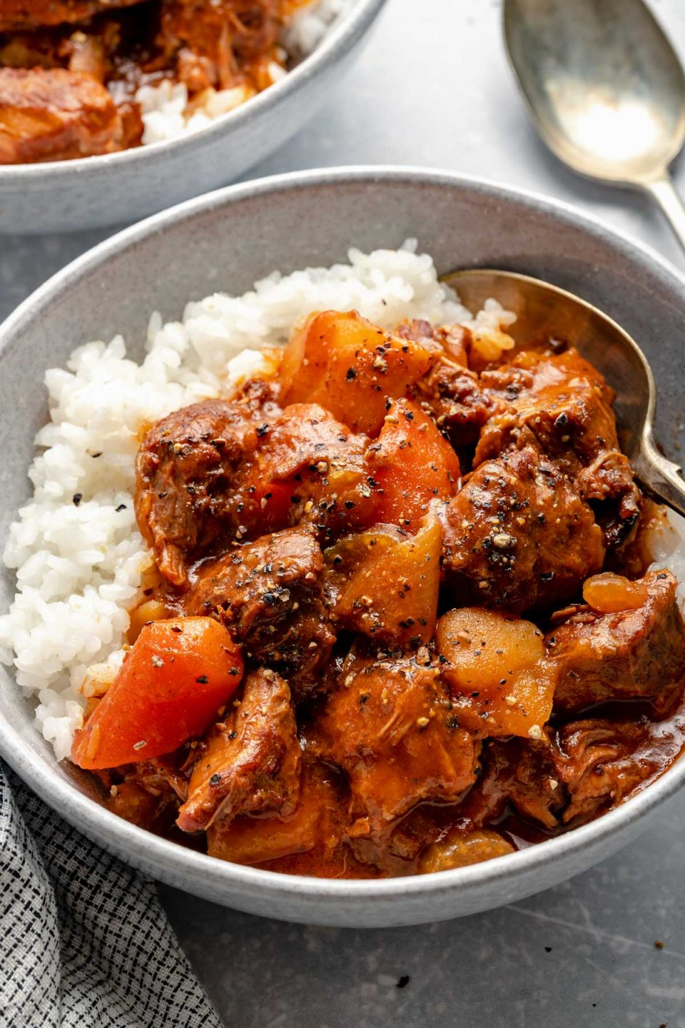 Side angle of Hawaiian style beef stew over sticky rice in a large bowl, which sits atop a light blue surface next to a checkered linen napkin, a spoon, & a second bowl of Hawaiian beef stew.