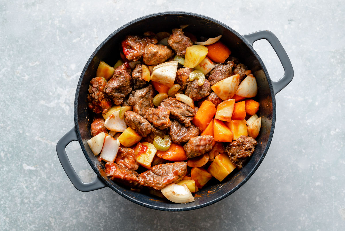 How to make Hawaiian Beef Stew, Step 3: Beef stew ingredients (browned beef, carrots, celery, onion, potatoes) mixed together in a large Dutch oven, which sits atop a light blue surface.