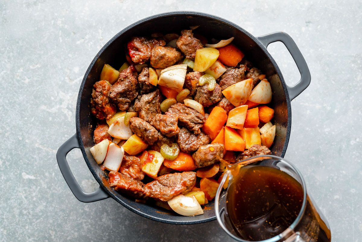 How to make Hawaiian Beef Stew, Step 3: Beef stew ingredients (browned beef, carrots, celery, onion, potatoes) mixed together in a large Dutch oven, which sits atop a light blue surface. Beef stock being poured into the Dutch oven from a large liquid measuring cup.