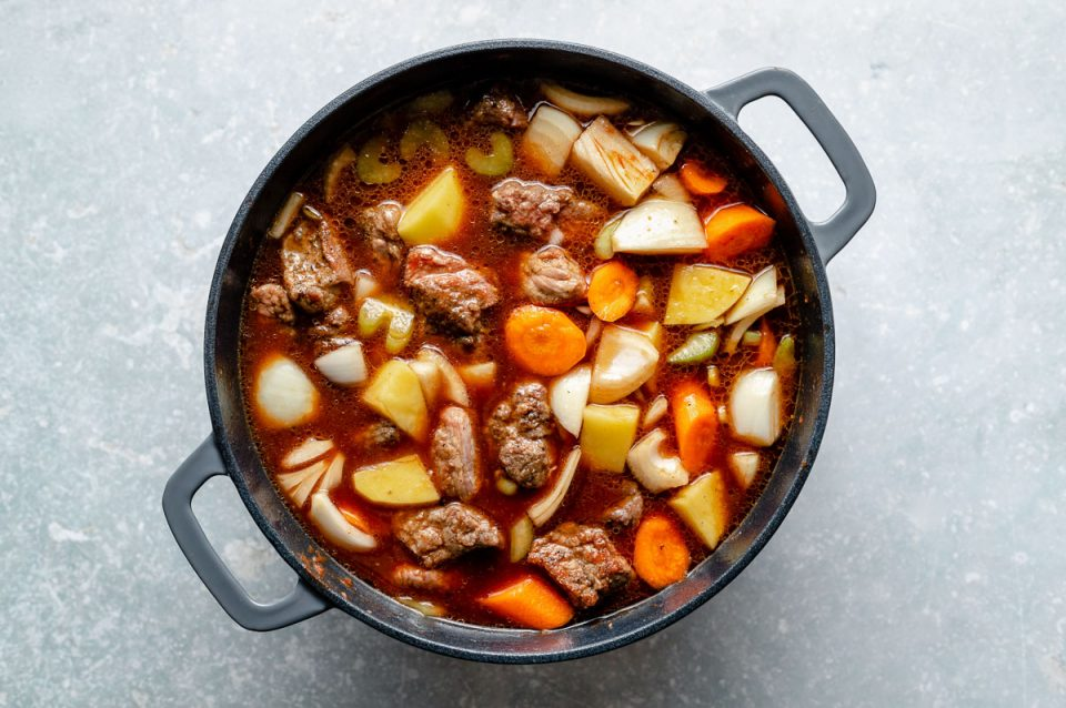 How to make Hawaiian Beef Stew, Step 3: Beef stew ingredients (browned beef, carrots, celery, onion, potatoes, beef stock) mixed together in a large Dutch oven, which sits atop a light blue surface.