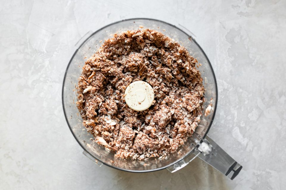 A food processor bowl containing finely chopped cremini mushrooms for mushroom duxelles. The bowl sits atop a white surface.