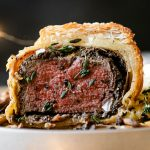 Straight on angle of Mini Beef Wellington, cut open to show the inside of the pastry. The beef wellington is on a white ceramic plate, served with mashed potatoes & roasted mushrooms. The plate sits atop a black surface. In the foreground are gold flatware & twinkly lights. In the background are a glass of white wine & a plaid linen napkin.