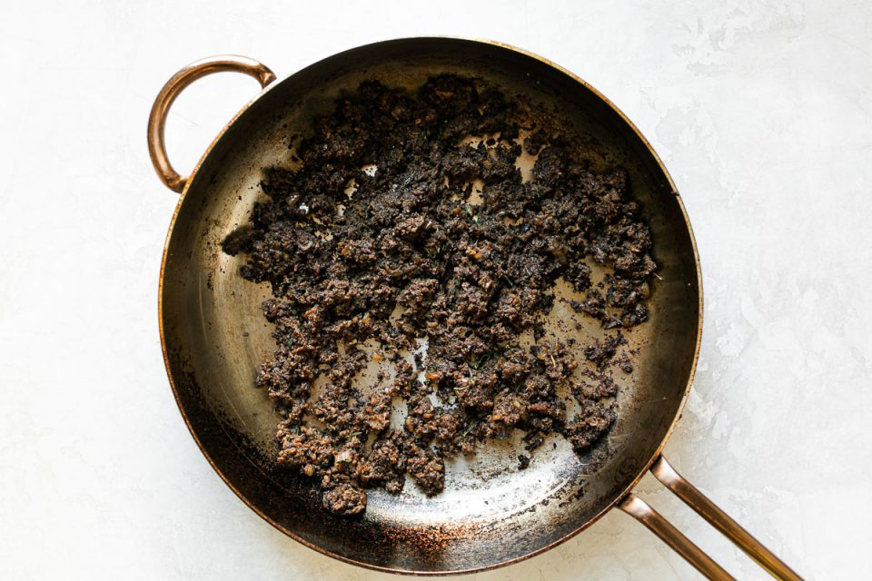 Mushroom duxelles in a large skillet atop a white surface.