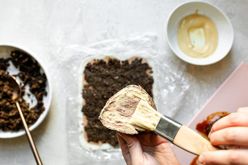 Individual Beef Wellington assembly: brushing individual filet mignon steak with Dijon mustard.