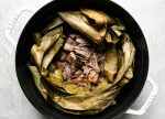 Shredded Kalua pig shown inside dried banana leaf in a white Dutch oven atop a creamy cement surface.