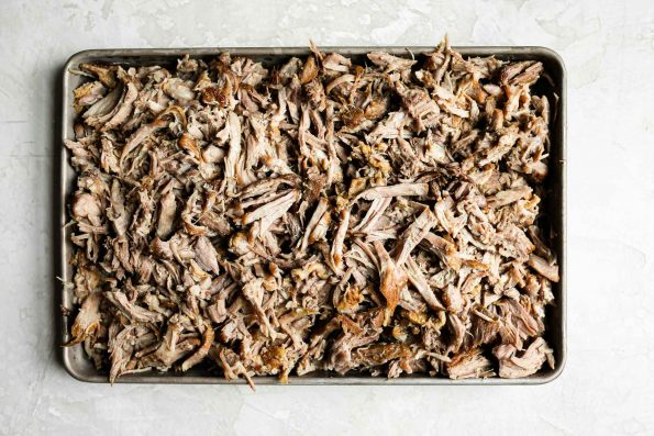 Shredded kalua pork on a small baking sheet sitting atop a creamy cement backdrop.