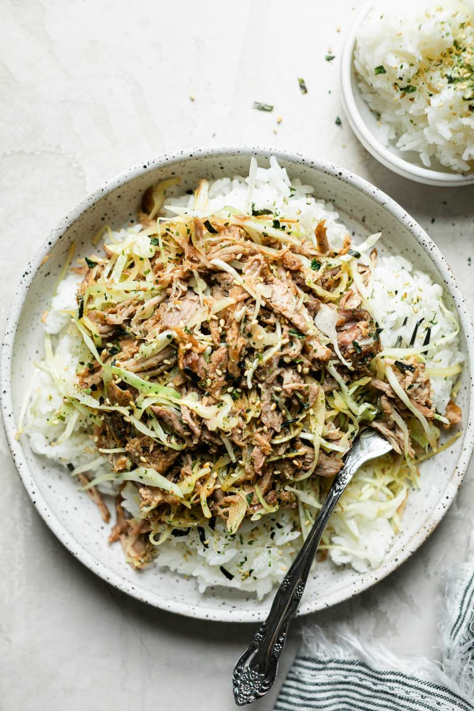 Kalua pork and cabbage served over white rice in a speckled ceramic bowl. The bowl sits atop a cream backdrop, next to a small bowl of white rice & a striped linen napkin.