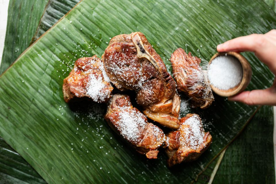 Browned pork shoulder sits atop vibrantly green banana leaf. A woman's hand reaches into the frame with a small bowl of Hawaiian salt, sprinkling the salt over the pork.