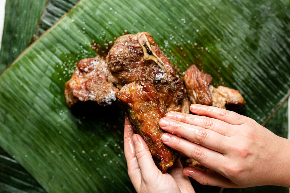 Browned pork shoulder sits atop vibrantly green banana leaf. A woman's hands hold one of the pieces of pork, rubbing the seasoning into the surface.