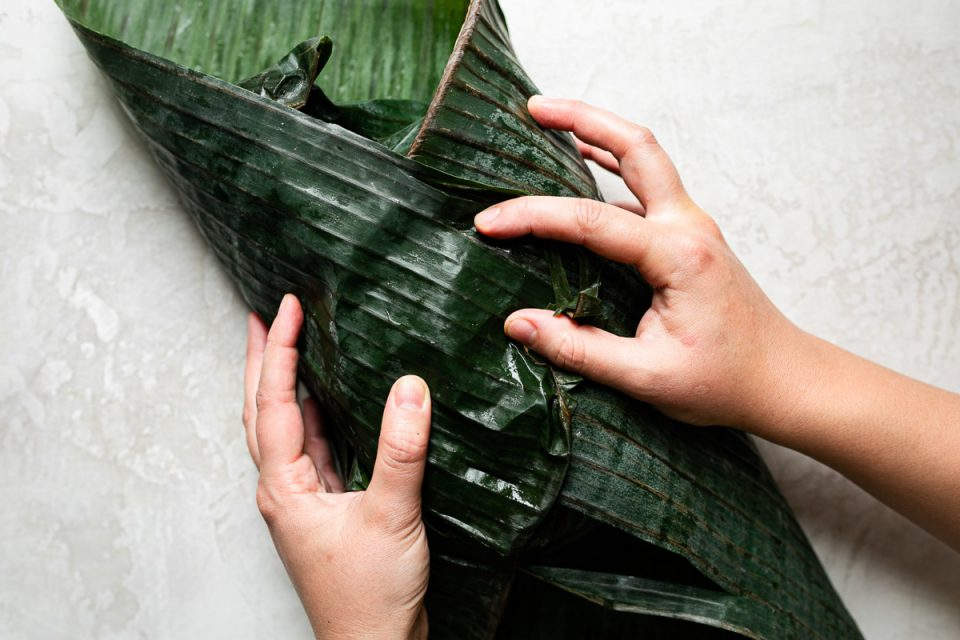 A woman's hands folding banana leaf around seasoned browned pork.