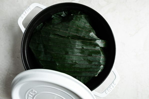 Banana leaf-wrapped pork shown in a white Dutch oven atop a creamy cement surface.