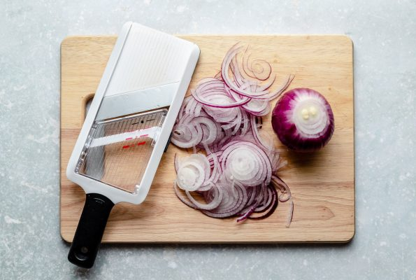 An overhead shot of a wood cutting board that sits on a light blue surface. On top of the cutting board is a handheld mandolin slicer, a pile of raw red onion that has been thinly sliced, and a partially sliced raw red onion.