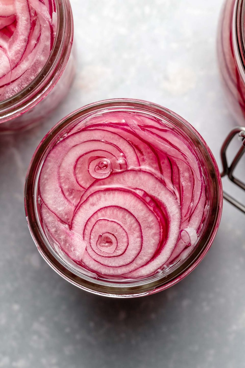 An overhead shot of thinly sliced rings of red onion inside of a mason jar and submerged in pickling liquid. The jar is set on a light blue surface. 2 other jars of easy pickled red onions are also partially shown.