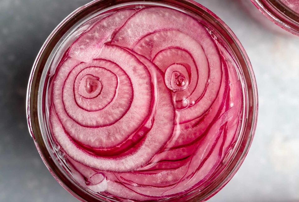 An overhead shot of thinly sliced rings of red onion inside of a mason jar and submerged in pickling liquid. The jar is set on a light blue surface.