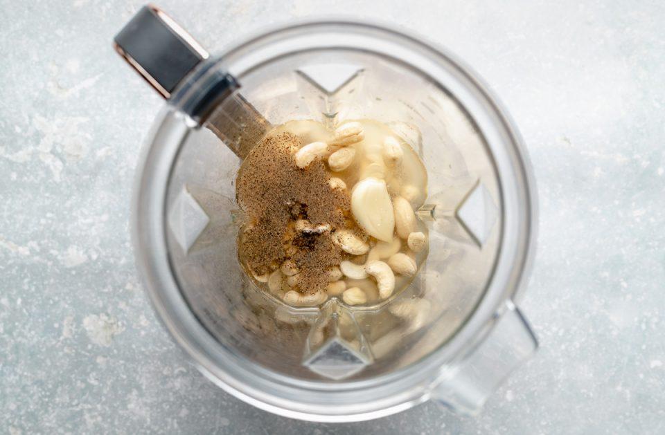 An overhead shot of Vegan Cashew Crema ingredients inside a high-speed blender carafe. Including raw cashews, garlic, lemon & lime juice, water, kosher salt & ground black pepper.
