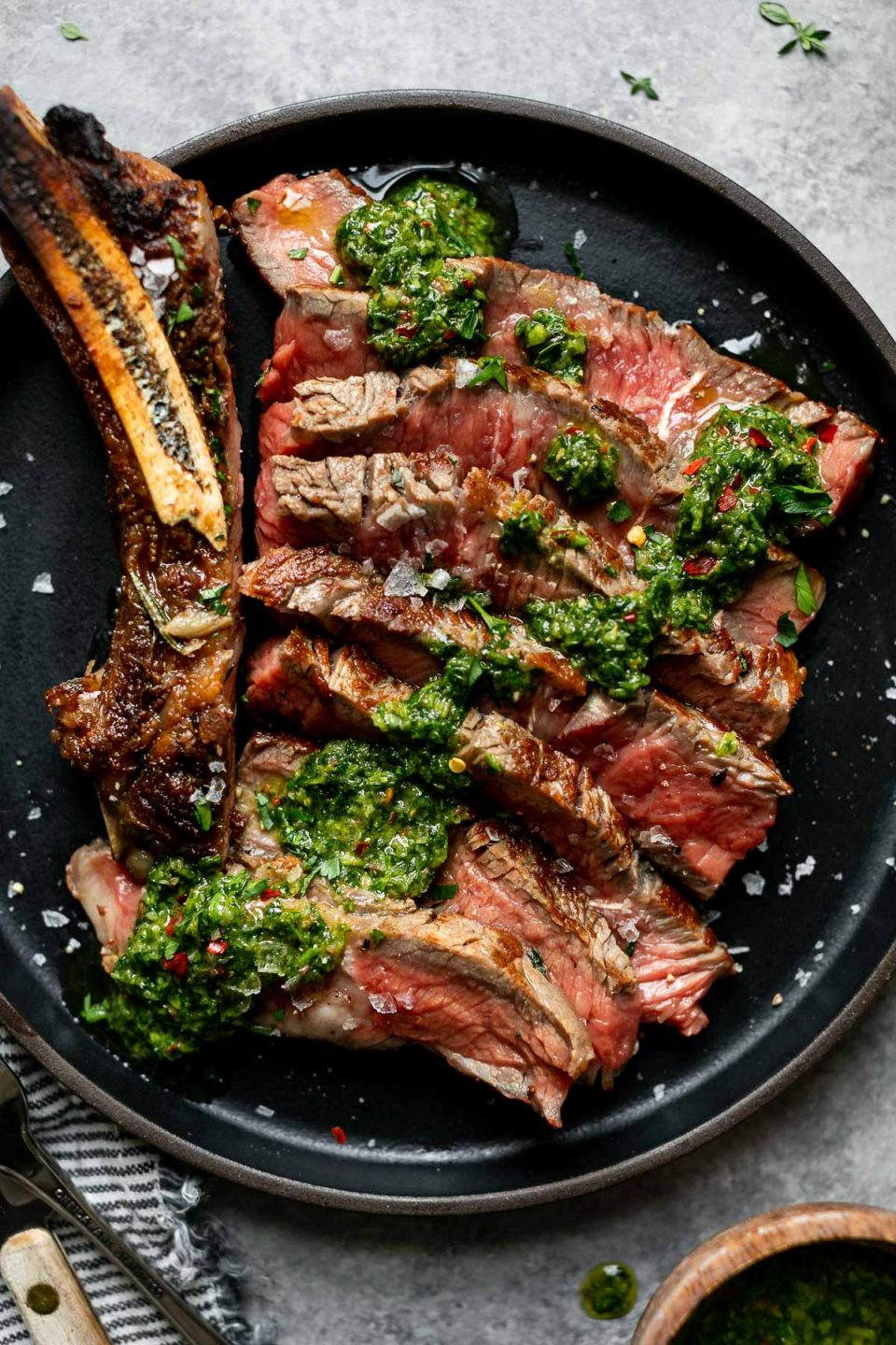 Cooked cast iron steak shown on a small black plate. The steak is sliced off the bone, showing a medium-rare interior, & topped with chimichurri. The plate is placed atop a light gray surface, next to a bowl of flaky salt, a striped linen napkin & a fork & steak knife.