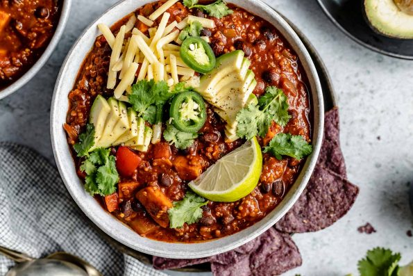Sweet Potato Quinoa Chili shown in 2 soup bowls, topped with avocado, jalapeno, shredded vegan cheese, lime wedges & cilantro leaves. The bowls sit atop a light blue surface, next to a checkered blue & white linen, soup spoons, garnishes (sliced jalapeno, lime wedges, tortilla chips, etc.).