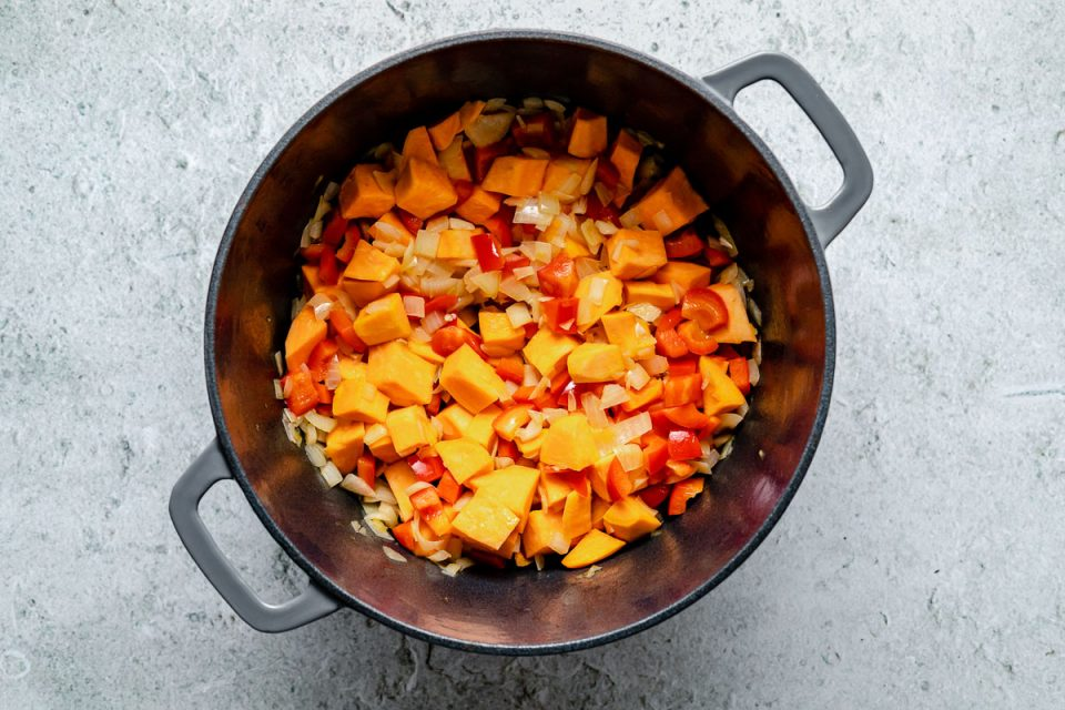 How to make Sweet Potato Quinoa Chili - Step 1: Onions, bell pepper, & sweet potato cooking in a large gray Dutch oven, which sits atop a light blue surface.