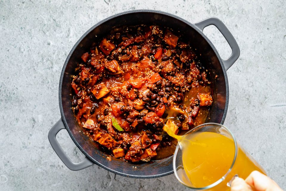 How to make Sweet Potato Quinoa Chili - Step 3: Veggie stock poured over quinoa chili ingredients in a large gray Dutch oven, which sits atop a light blue surface.