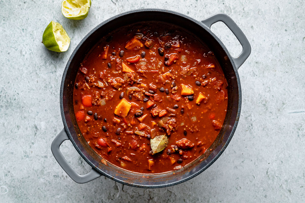 How to make Sweet Potato Quinoa Chili - Step 3: Sweet potato quinoa chili, after simmering, in large gray Dutch oven, which sits atop a light blue surface.