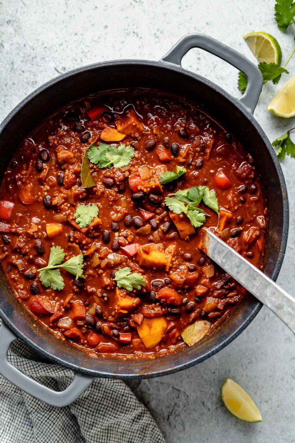 Sweet Potato Quinoa Chili in a large gray Dutch oven, topped with fresh cilantro leaves. The Dutch oven sits atop a light blue surface, next to a checkered black & white linen & lime wedges.