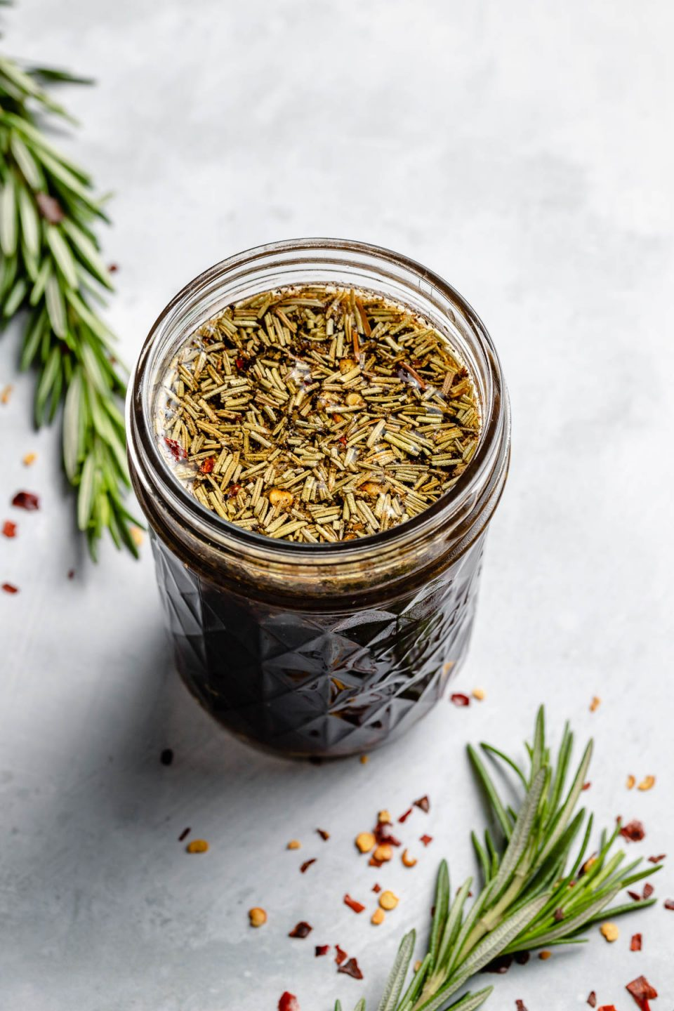 Brown Sugar Bourbon marinade shown in a small ball jar, sitting atop a light blue surface with a fresh sprig of rosemary & crushed red chili pepper flakes on the surface in the foreground & in the background.