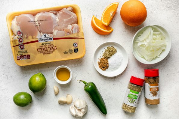 Chicken carnitas ingredients arranged on a white surface: Kirkwood Chicken thighs from ALDI, limes, olive oil, garlic, jalapeno, Stonemill cumin & oregano bottles from ALDI, sliced onion & orange.