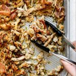 Shredded crispy chicken carnitas on a small silvery baking sheet, which sits atop a white surface. A woman's hand reaches into the frame with small tongs, scooping up some of the chicken carnitas.