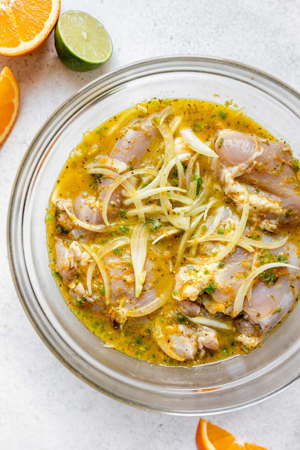 How to make chicken carnitas, Step 1: Chicken thighs & yellow onion marinating in citrus & jalapeno carnitas sauce in a large glass bowl, which sits atop a white surface next to sliced oranges & limes.