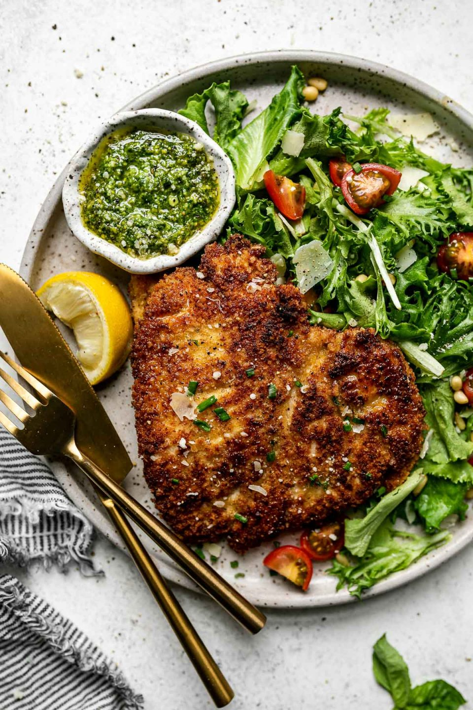 Parmsean chicken breast on a large plate with a green salad & a small bowl of pesto. The plate sits atop a white surface, next to a gray striped linen napkin.