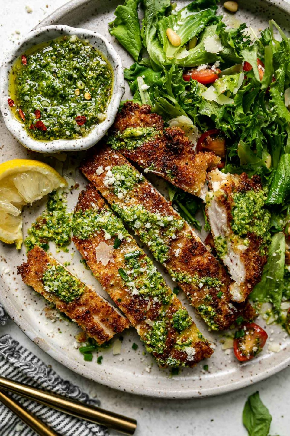 Sliced oparmsean chicken breast, topped with pesto & parmesan cheese, on a large plate with a green salad & a small bowl of pesto. The plate sits atop a white surface, next to a gray striped linen napkin.