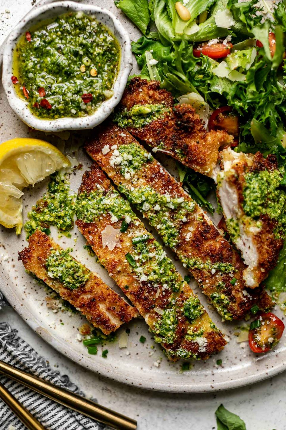 Close up of sliced parmsean chicken breast, topped with pesto & parmesan cheese, on a large plate with a green salad & a small bowl of pesto. The plate sits atop a white surface, next to a gray striped linen napkin.