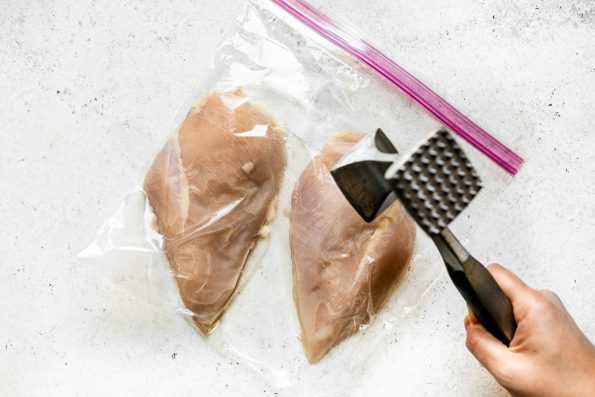 How to make parmesan crusted chicken, Step 1: Chicken breasts in a large plastic bag on a white surface. A woman's hand reaches into the frame with a meat mallet, pounding them flat.