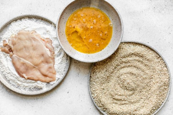 How to make parmesan crusted chicken, Step 2: A breading station of flour, egg, & parmesan-breadcrumbs in large gray ceramic dishes atop a white surface. One chicken cutlet is in the flour mixture.