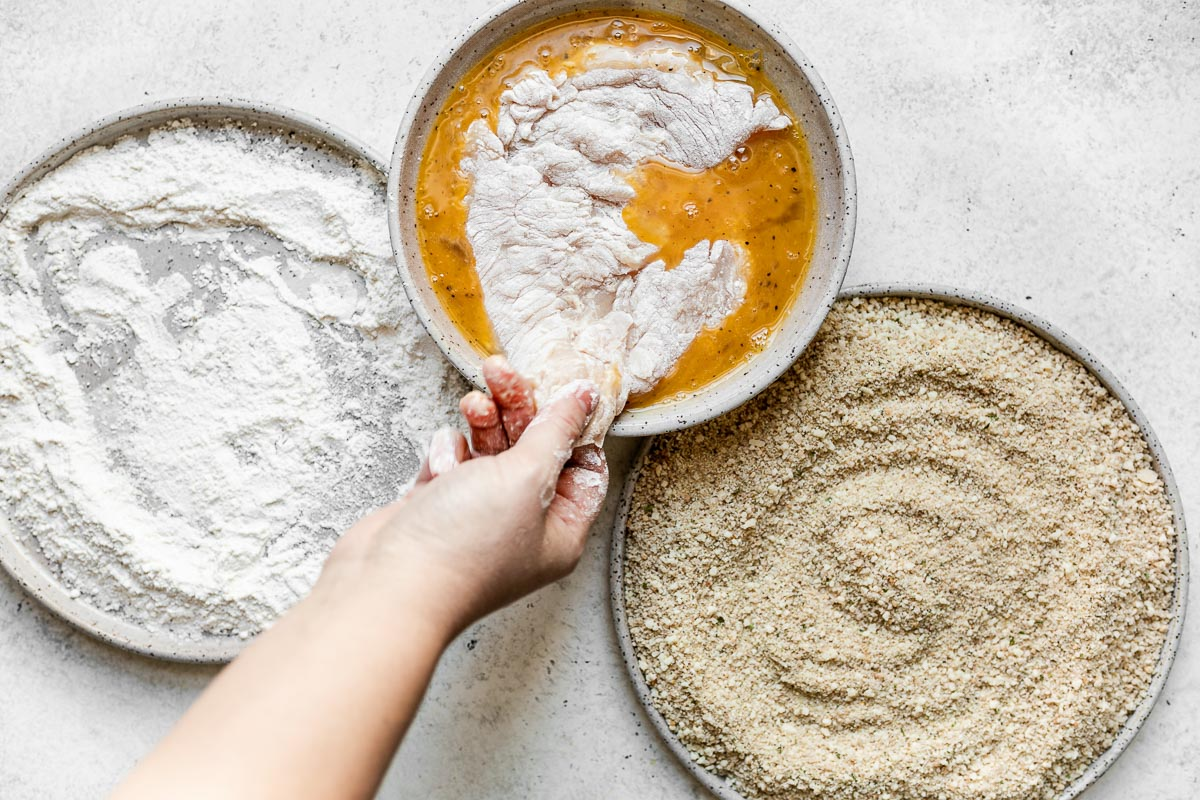 How to make parmesan crusted chicken, Step 3: A breading station of flour, egg, & parmesan-breadcrumbs in large gray ceramic dishes atop a white surface. A woman's hand places one chicken cutlet is in the egg mixture.