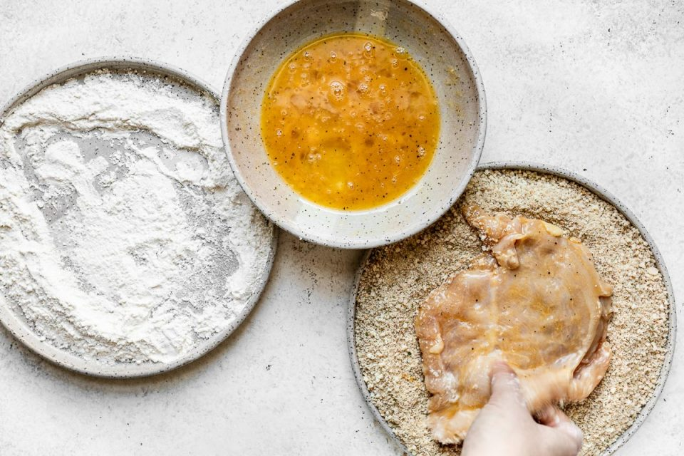 How to make parmesan crusted chicken, Step 3: A breading station of flour, egg, & parmesan-breadcrumbs in large gray ceramic dishes atop a white surface. A woman's hand places one chicken cutlet is in the parmesan-panko mixture.