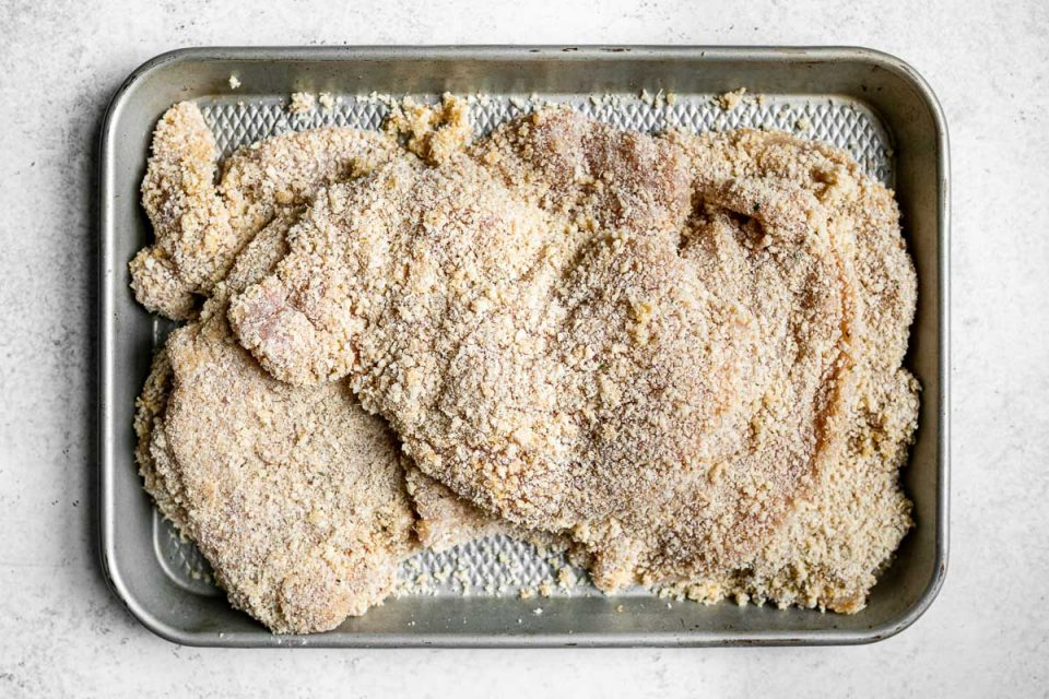 Breaded parmesan-crusted chicken cutlets on a silver quarter baking sheet, atop a white surface.