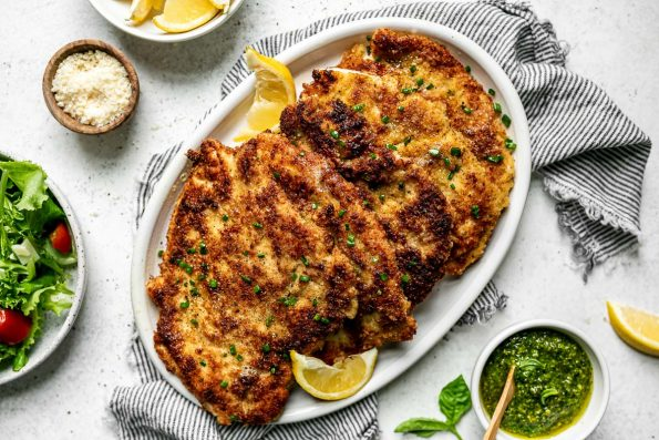 Parmesan crusted chicken cutlets on a large white platter, which sits atop a gray striped linen napkin on a white surface, surrounded by salad, a bowl of lemon wedges, a small bowl of pesto, & a small bowl of grated parmesan cheese.