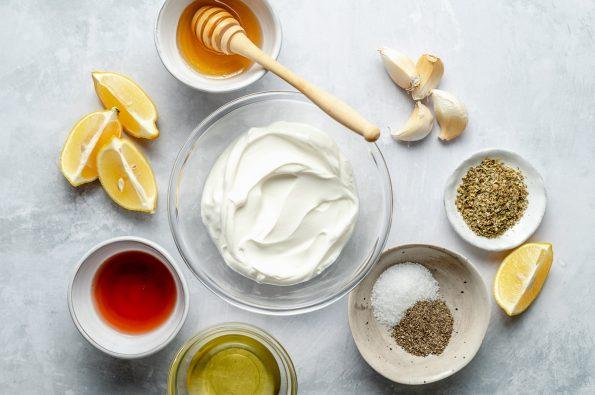 Greek marinade ingredients arranged on a light blue surface: greek yogurt, garlic, lemon, olive oil, red wine vinegar, honey, dried oregano, salt, & pepper.