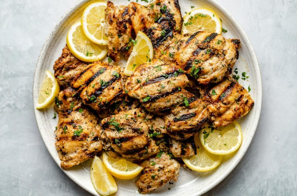 Grilled Greek chicken thighs shown on a white speckled plate atop a light blue surface. The chicken is garnished with fresh chopped herbs, lemon slices, & lemon wedges.