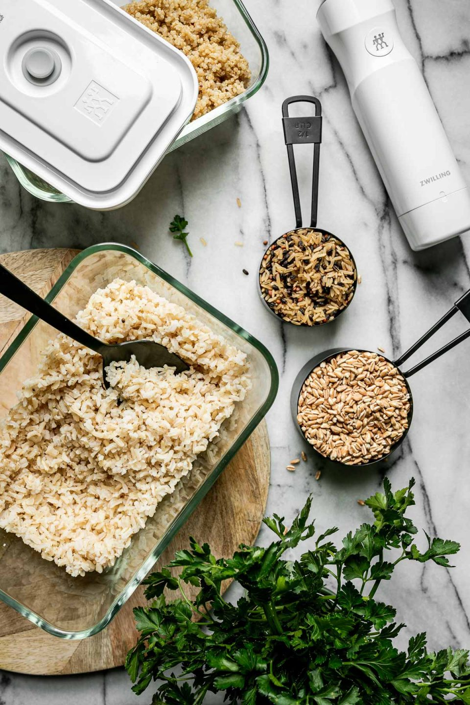Mise en Place with Zwilling Fresh & Save. Zwilling Fresh & Save containers sit atop a white marble surface, filled with cooked quinoa & brown rice. The containers are surrounded by measuring cups with grain blends & a bowl of fresh parsley.