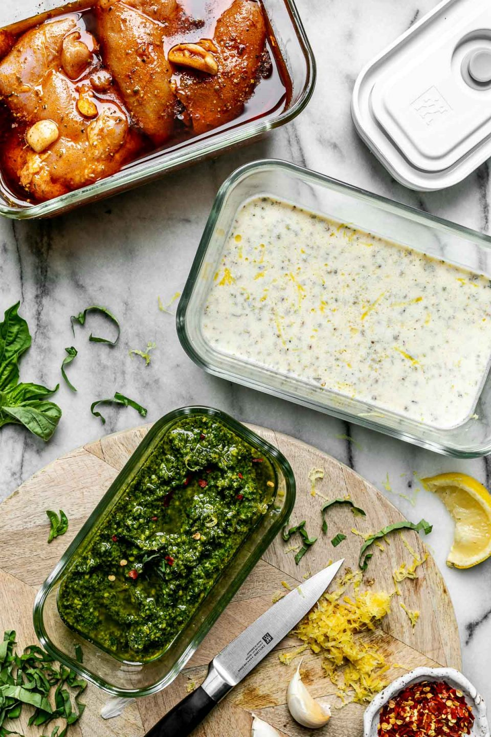 Mise en Place with Zwilling Fresh & Save. Zwilling Fresh & Save containers sit atop a white marble surface, filled with marinating chicken shawarma, Greek yogurt marinade, & fresh pesto. The containers are surrounded by fresh basil, lemon zest, garlic cloves & lemon wedges.