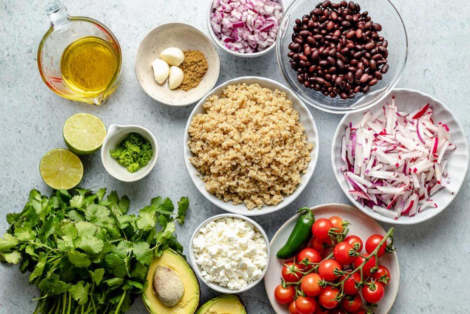 Southwest quinoa salad ingredients arranged on a light blue surface – olive oil, limes, lime zest, cilantro, avocado, queso fresco, quinoa, garlic, cumin, red onion, black beans, radish, jalapeno, & cherry tomatoes.