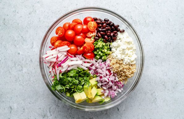 How to make Southwest Quinoa Salad, Step 2 – Assembly, all quinoa salad ingredients grouped together in large glass mixing bowl atop a light blue surface.