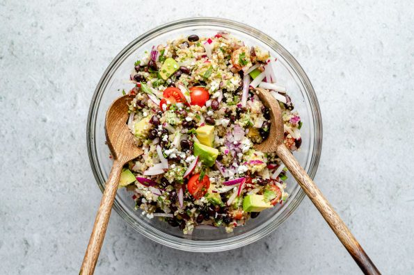 How to make Southwest Quinoa Salad, Step 2 – Southwest quinoa salad tossed together in a large glass mixing bowl atop a light blue surface with 2 wooden spoons nestled into the bowl.