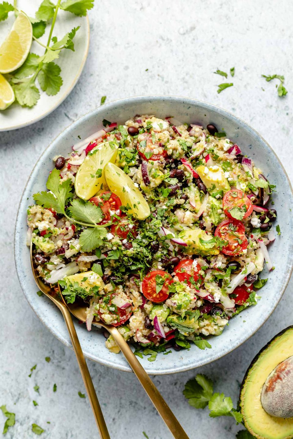 Southwest quinoa salad shown in light blue serving bowl, topped with fresh cilantro & lime wedges. Gold flatware is nestled into the quinoa salad for serving. The bowl sits atop a light blue surface, surrounded by chopped cilantro, lime wedges, & halved avocado.